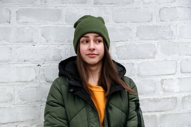 Retrato de uma linda garota surpreendida com um suéter amarelo e um chapéu cáqui, que fica perto de uma parede de tijolos brancos. o conceito de emoções.