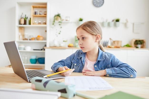 Retrato de uma linda garota usando laptop enquanto faz a lição de casa ou testes, sentado na mesa de madeira no interior aconchegante da casa, copie o espaço