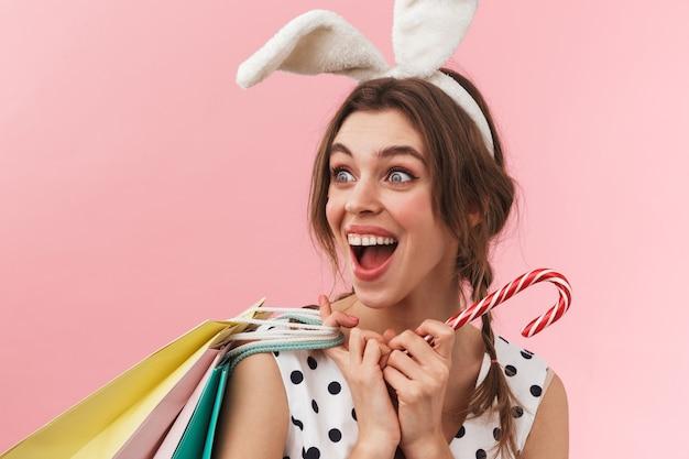 Retrato de uma linda garota usando orelhas de coelho, isolada, carregando sacolas de compras e segurando um bastão de doces