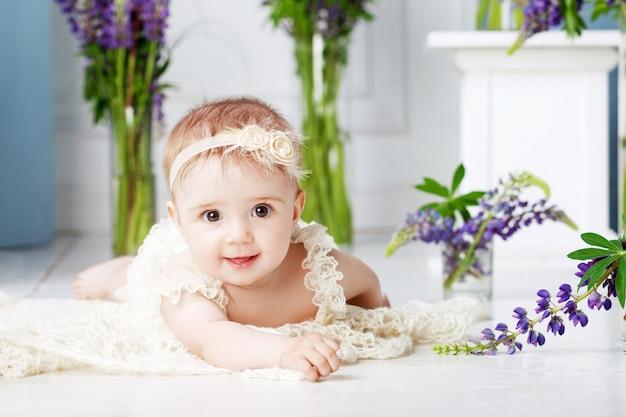 Retrato de uma linda garotinha com flores violetas. menina doce e sorridente deitada de bruços