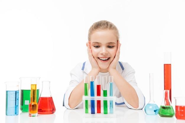 Retrato de uma linda garotinha com jaleco branco fazendo experimentos químicos com líquido multicolorido em tubos de ensaio isolados sobre a parede branca