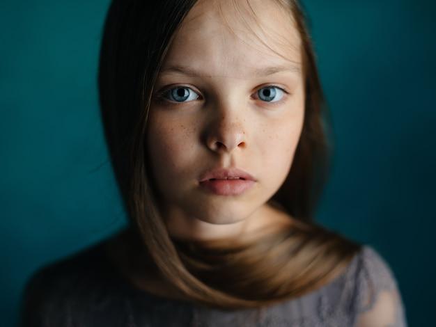 Retrato de uma linda garotinha em um vestido cinza em uma visão recortada em close-up azul de