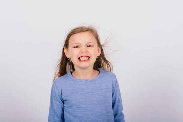 Retrato de uma linda garotinha feliz sorrindo em a. fundo branco isolado