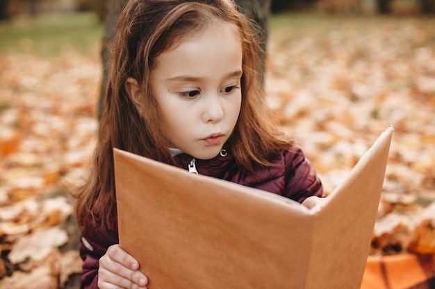 Retrato de uma linda garotinha lendo um bookg otudoor no parque.