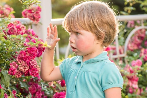 Retrato de uma linda garotinha loira com flores rosas. alergia à floração