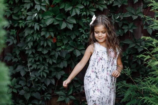 Retrato de uma linda garotinha na natureza num dia de verão. brincando no parque com os pais. fechar-se.
