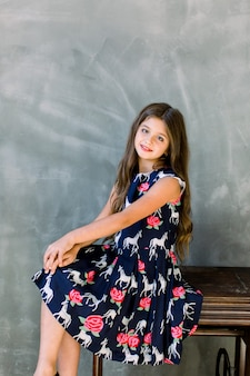 Retrato de uma linda garotinha sorridente. a menina senta-se em uma máquina de costura antiga de madeira em uma parede cinza com espaço de cópia