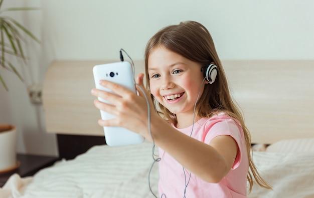 Retrato de uma linda garotinha sorrindo para o smartphone, tomando selfie