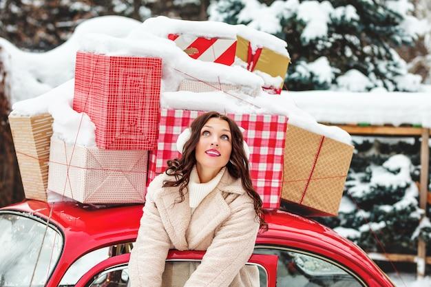 Retrato de uma linda jovem adulta alegre e feliz no carro vermelho com presentes