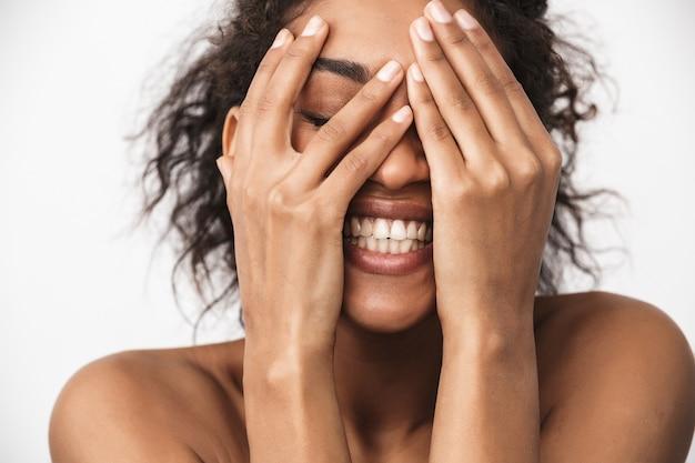 Retrato de uma linda jovem africana feliz posando isolado sobre a parede branca, cobrindo o rosto com as mãos.