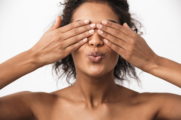 Retrato de uma linda jovem africana feliz posando isolado sobre a parede branca, cobrindo os olhos com as mãos mandando beijos.