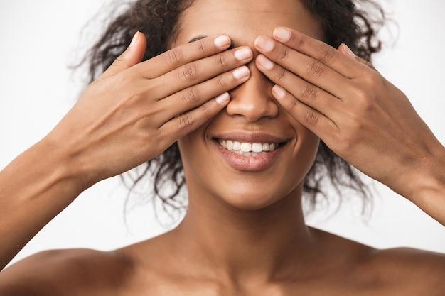 Retrato de uma linda jovem africana feliz posando isolado sobre a parede branca, cobrindo os olhos com as mãos.