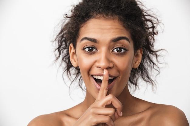 Retrato de uma linda jovem africana feliz posando isolado sobre uma parede branca, mostrando o gesto de silêncio.