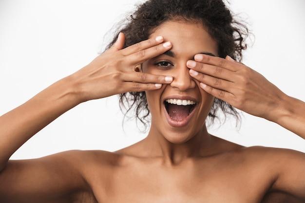 Retrato de uma linda jovem africana feliz posando isolado sobre uma parede branca.