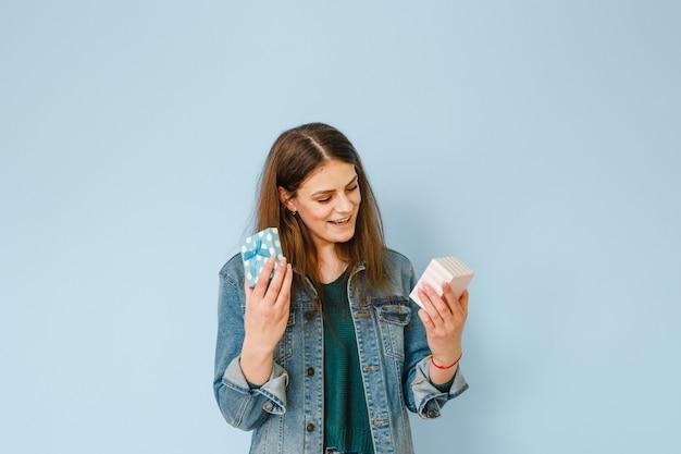 Retrato de uma linda jovem animado segurando um presente e feliz sobre fundo azul