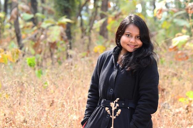 Retrato de uma linda jovem ao ar livre no parque na temporada de inverno