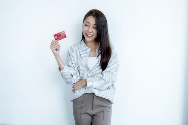 Retrato de uma linda jovem asiática com cabelo comprido, segurando um cartão de crédito vermelho, os olhos brilhando para a câmera. pronto para pagar compras de acordo com produtos com desconto.