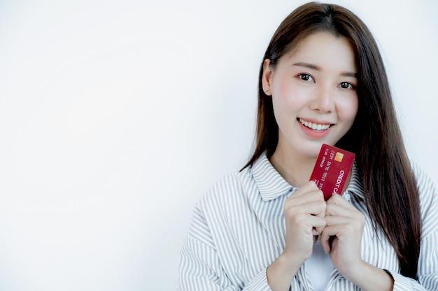 Retrato de uma linda jovem asiática com cabelo comprido, segurando um cartão de crédito vermelho, os olhos brilhando para a câmera. pronto para pagar compras de acordo com produtos com desconto
