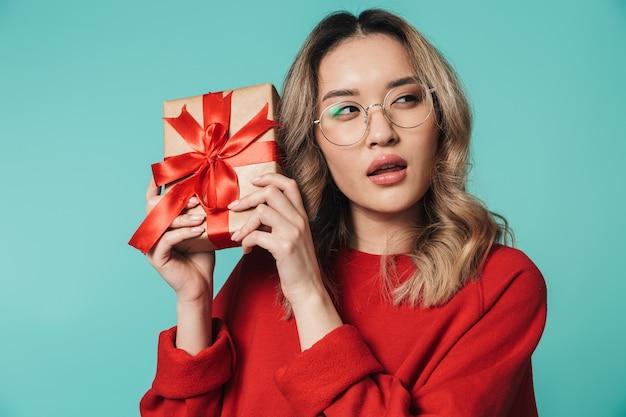 Retrato de uma linda jovem asiática em pé, isolada sobre uma parede azul, mostrando uma caixa de presente