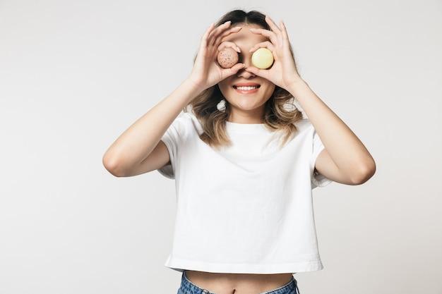 Retrato de uma linda jovem asiática em pé, isolada sobre uma parede branca, segurando biscoitos no rosto