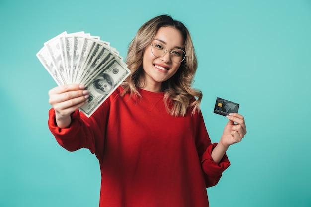Retrato de uma linda jovem asiática em pé isolado sobre uma parede azul, mostrando notas de dinheiro e cartão de crédito