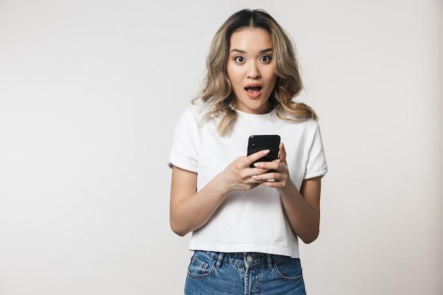 Retrato de uma linda jovem asiática feliz em pé isolado sobre uma parede branca, usando telefone celular