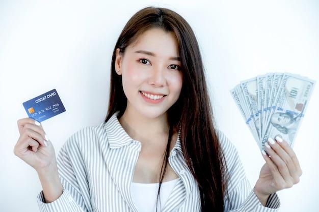 Retrato de uma linda jovem asiática linda mulher com cabelo comprido, segurando um cartão de crédito azul e uma nota de dólar, os olhos brilhando para a câmera pronta para pagar as compras de acordo com os produtos com desconto.