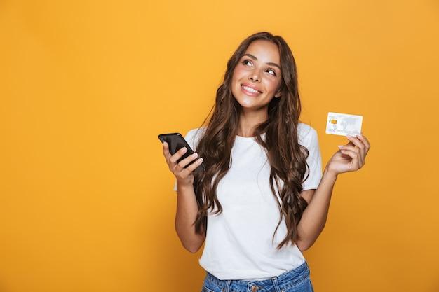 Retrato de uma linda jovem com longos cabelos castanhos em pé sobre uma parede amarela, segurando um telefone celular, mostrando um cartão de crédito de plástico