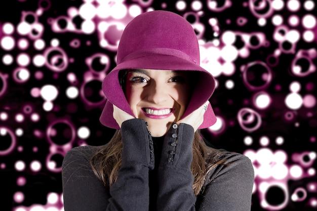 Retrato de uma linda jovem com um chapéu granada na cabeça, na frente do fundo de holofotes