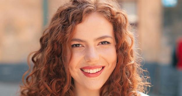 Retrato de uma linda jovem de etnia caucasiana, com cabelo ruivo cacheado, em pé no calor.