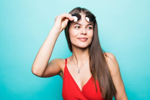 Retrato de uma linda jovem de óculos escuros em uma parede azul