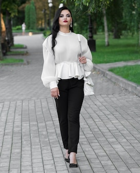 Retrato de uma linda, jovem e atraente menina morena caucasiana. menina elegante posando no verão no parque. conceito de moda.