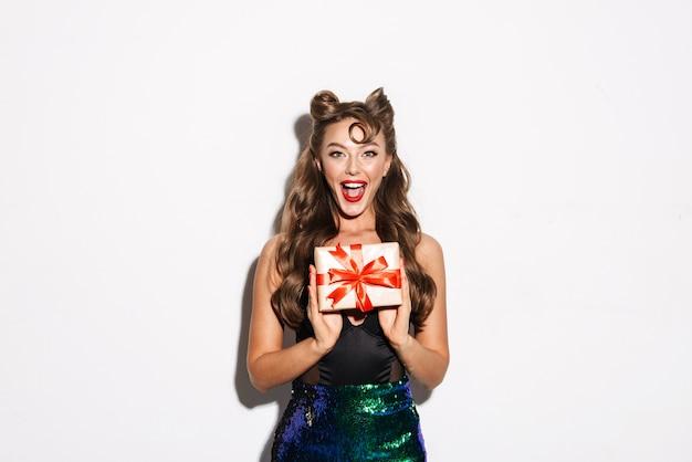 Retrato de uma linda jovem e sedutora garota pin-up usando um vestido de pé isolado, mostrando uma caixa de presente