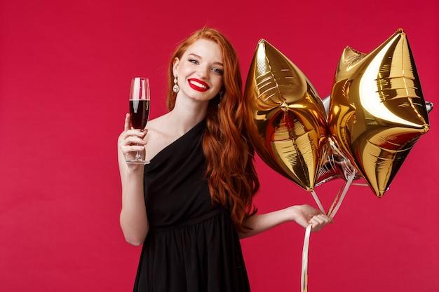 Retrato de uma linda jovem elegante com batom vermelho, cabelo ruivo e vestido preto, segurando balões e taça de champanhe, dizendo brinde para amigo ter aniversário sorrindo alegre