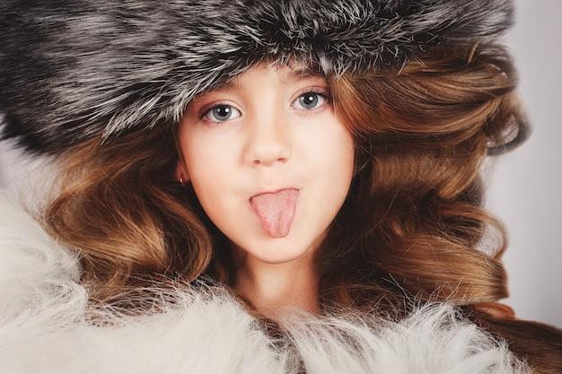 Retrato de uma linda jovem em boné de pele coloca a língua para fora