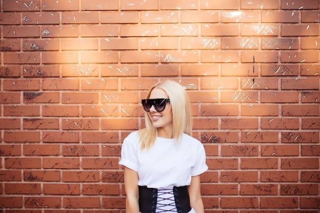 Retrato de uma linda jovem em óculos de sol vermelhos sobre uma parede de tijolo vermelho