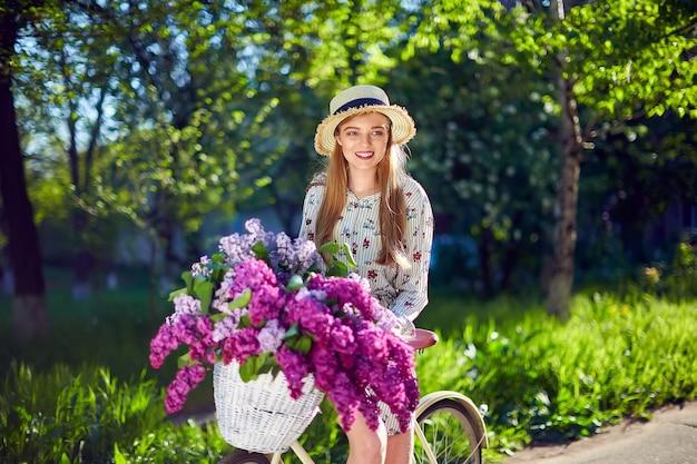 Retrato de uma linda jovem feliz com bicicleta vintage e flores no fundo da cidade à luz do sol ao ar livre. bicicleta com cesto cheio de flores. conceito de lazer ativo.