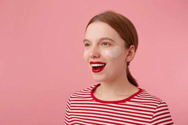 Retrato de uma linda jovem feliz ruiva com lábios vermelhos e com manchas sob os olhos, usa uma camiseta listrada vermelha, desvia o olhar e sorri amplamente.