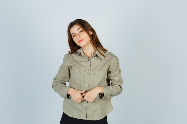 Retrato de uma linda jovem fêmea de mãos dadas na frente dela, curvando a cabeça no ombro na camisa, saia e olhando pensativa para a frente