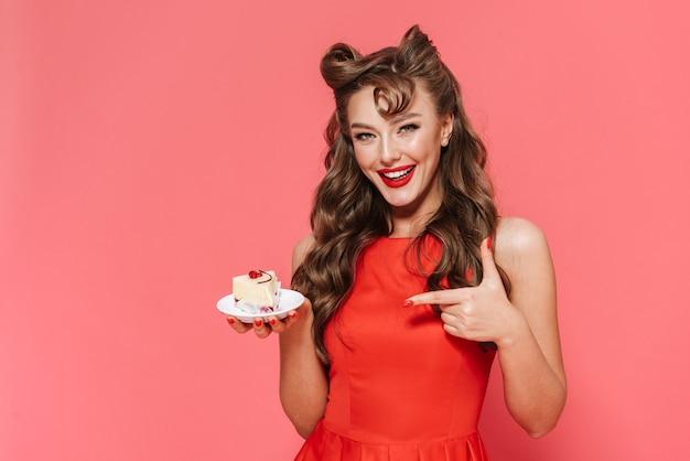 Retrato de uma linda jovem garota pin-up usando um vestido de pé isolado, comendo sobremesa