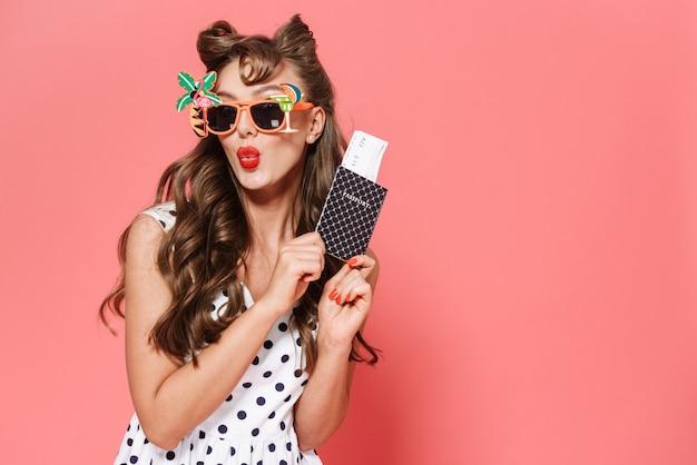 Retrato de uma linda jovem garota pin-up usando um vestido de pé isolado, mostrando o passaporte com a passagem aérea