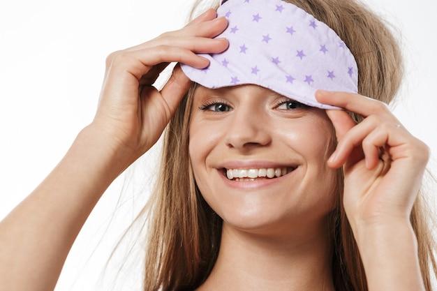 Retrato de uma linda jovem loira seminua usando máscara de dormir sorrindo isolado no branco
