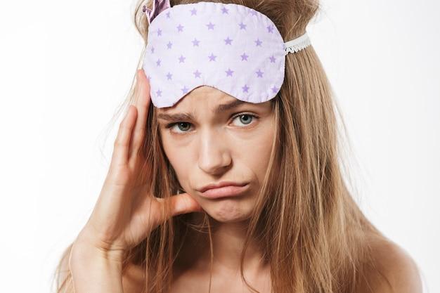 Retrato de uma linda jovem loira seminua usando máscara de dormir triste isolado no branco