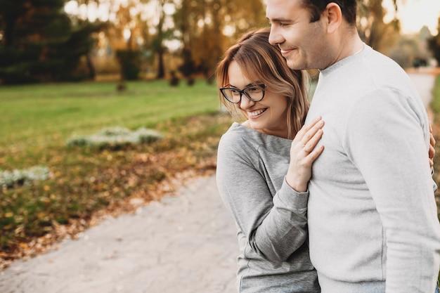 Retrato de uma linda jovem mãe abraçando o marido enquanto olha para os filhos que brincam ao ar livre no parque.