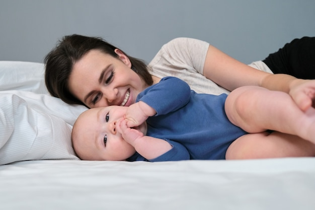 Retrato de uma linda jovem mãe e seu bebê, deitados na cama juntos