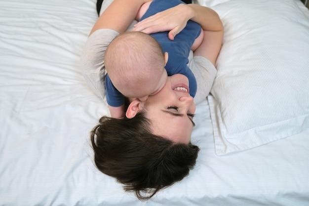 Retrato de uma linda jovem mãe e seu filho de 7 meses, pai e bebê deitados na cama juntos, vista de cima