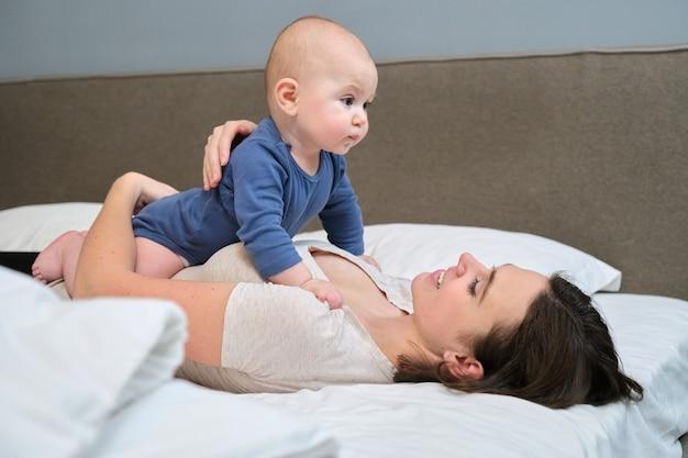 Retrato de uma linda jovem mãe e seu filho de 7 meses, pai e bebê deitados na cama