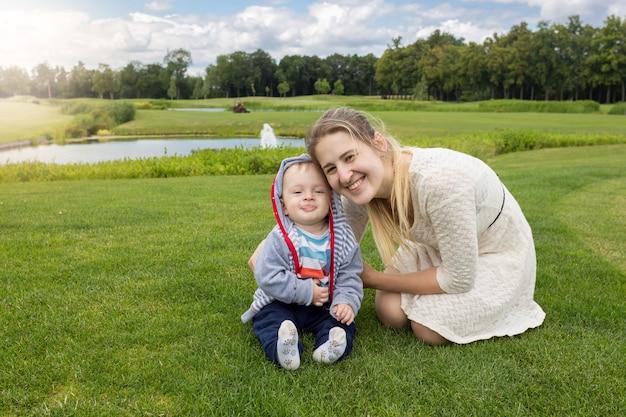 Retrato de uma linda jovem mãe e um alegre menino de 9 meses relaxando na grama no parque