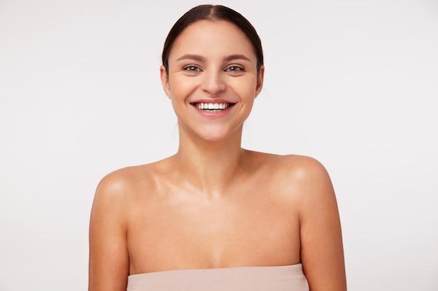Retrato de uma linda jovem morena alegre com maquiagem natural, parecendo feliz com um largo sorriso, vestindo blusa nude em pé