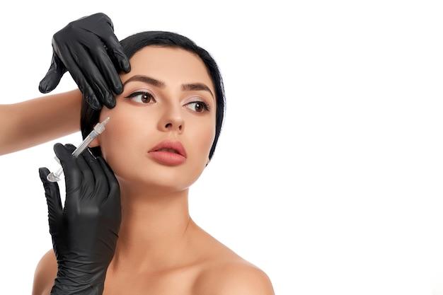 Retrato de uma linda jovem morena com injeção de beleza com seringa por esteticista profissional